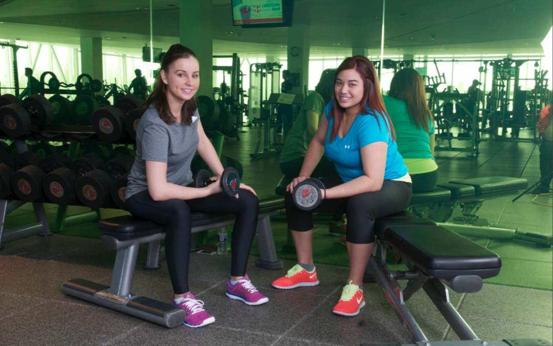 Two woman working out at the AWC in front of a green mirror
